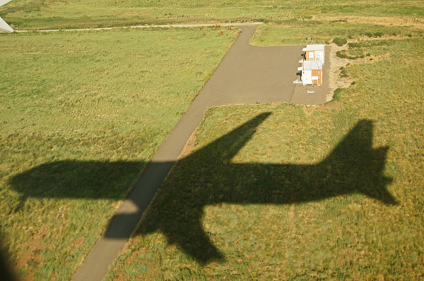 plane landing shadow grass denver airport