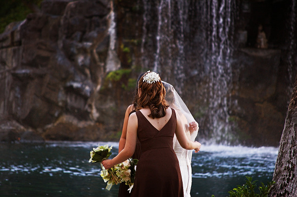 Bride and maids in front of waterfall in Waikoloa Village