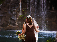 big-island-hawaii > Bride and maids in front of waterfall in Waikoloa Village