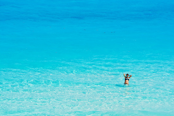 Girl alone in clear turquoise water at the beach of Cancún Mexico