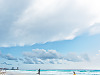 cancun-mexico-2014 > Couple of beachgoers running on the beach with the waves and clouds in Cancún