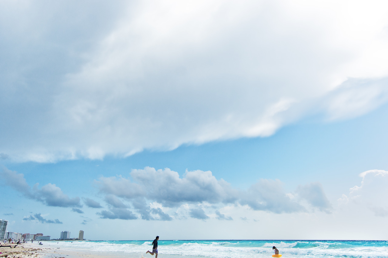 Couple of beachgoers running on the beach with the waves and clouds in Cancún