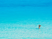 cancun-mexico-2014 > Girl alone in clear turquoise water at the beach of Cancún Mexico