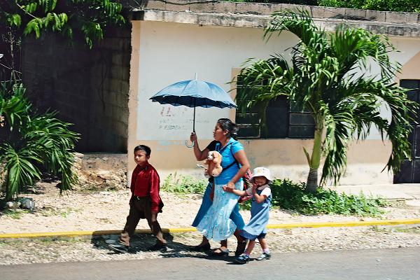 Family walking with umbrella a street scene in Yucatan Mexico