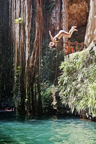 chichen-itza-valladolid-yucatan  > Girl in swimsuit jumping head first in the water of Cenote Ik Kil in Yucatan