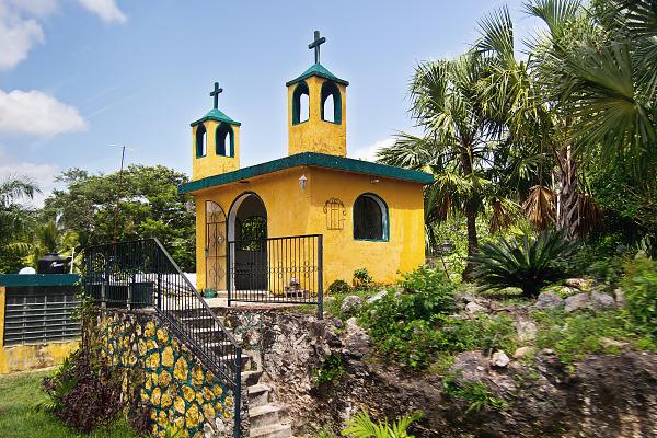Yellow and green miniature church a street scene in Yucatan Mexico