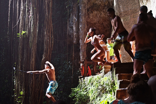 Young people jumping together in the water of Cenote Ik Kil in Yucatan