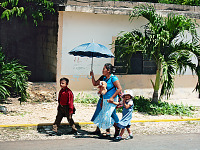 chichen-itza-valladolid-yucatan > Family walking with umbrella a street scene in Yucatan Mexico
