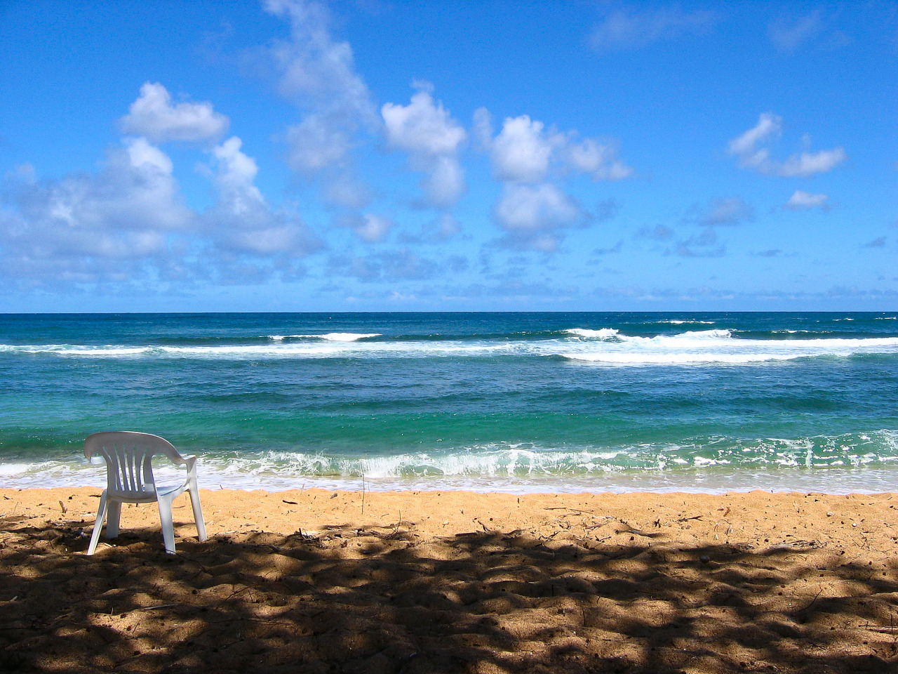 Blue waves crashing on the beach in Kauai, Hawaii