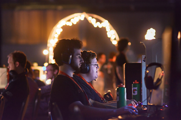 Gamers playing in front of light arch - Quakecon BYOC
