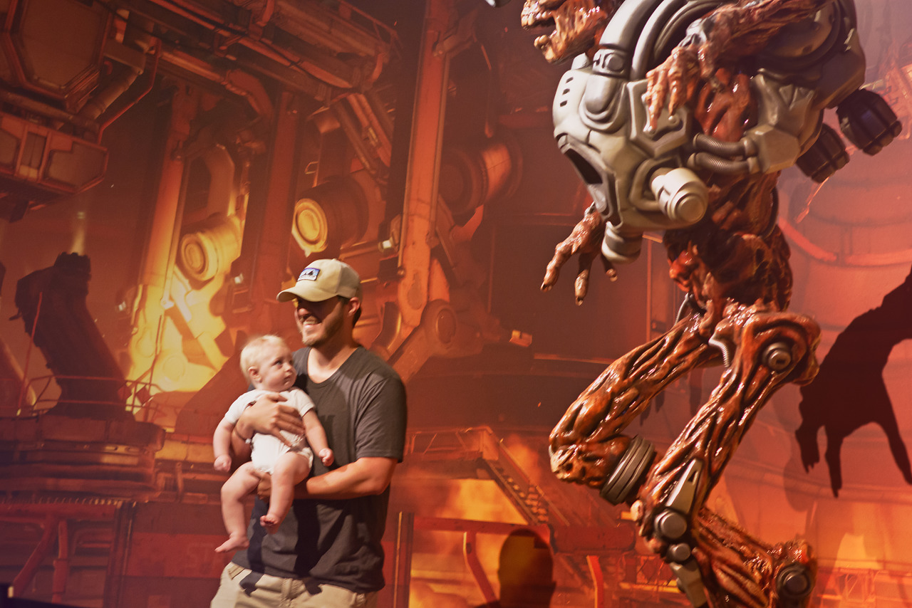 Baby looking at real life statue of Doom revenant on the Quakecon showfloor