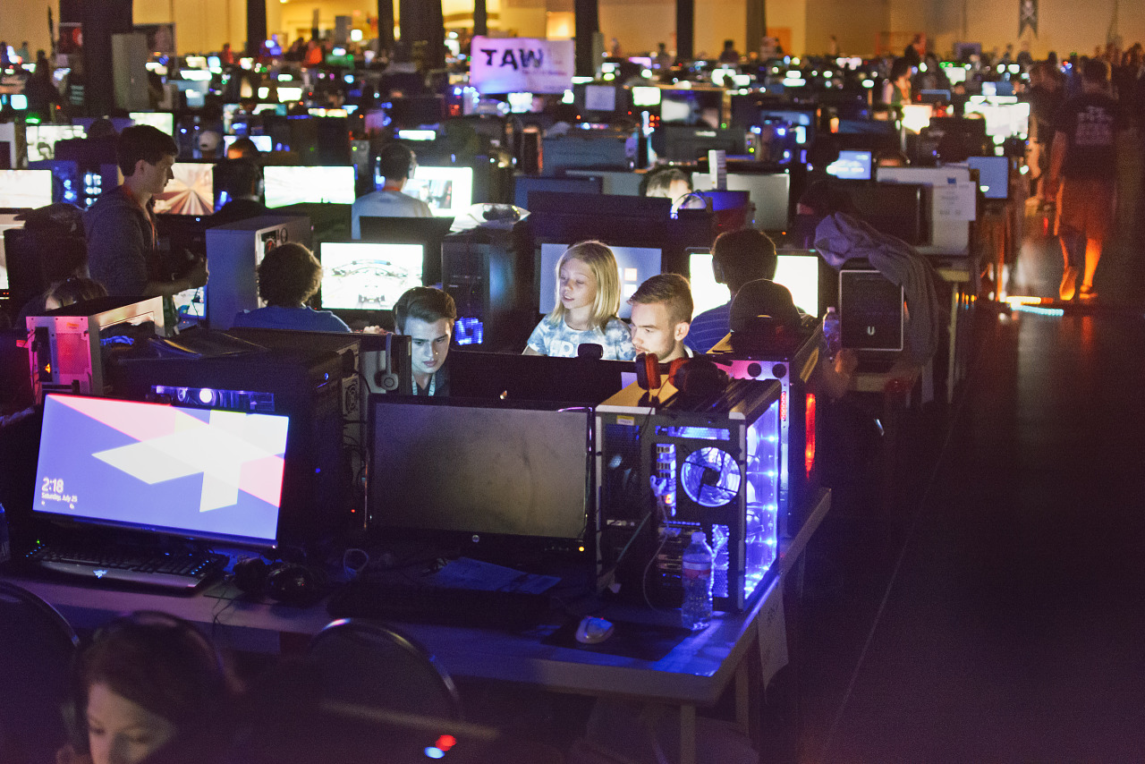 Gamers with child at the Quakecon BYOC lit by monitors
