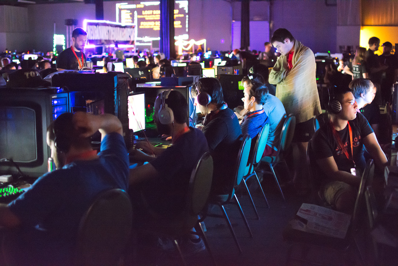 Row of PC Gamers lit by monitors in BYOC area of Quakecon
