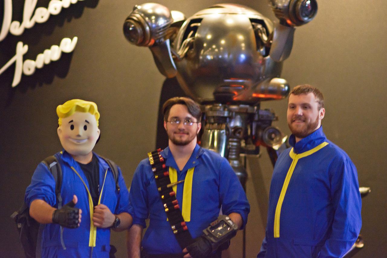 Three vault dwellers cosplay in front of Mr Handy Showfloor Quakecon 2015