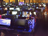 quakecon-dallas-2015 > Gamers with child at the Quakecon BYOC lit by monitors