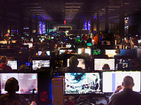 quakecon-dallas-2015 > Room full of PCs lit with monitors at the BYOC LAN Party of Quakecon