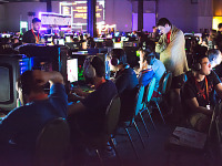 quakecon-dallas-2015 > Row of PC Gamers lit by monitors in BYOC area of Quakecon