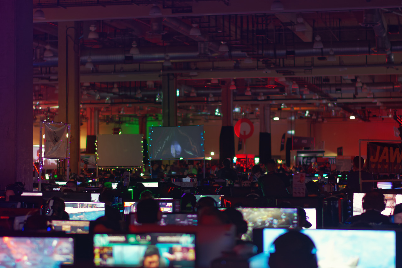 Clan banners hovering over lit computer screens in BYOC area of Quakecon 2017