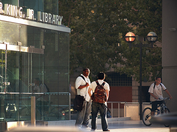 Two males talking in front of Martin Luther King, Jr Library at SJSU