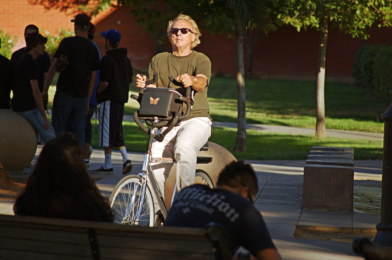 Man on bicycle with sunglasses on San Jose Campus