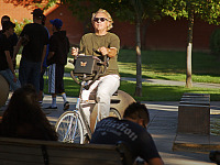 san-jose-state > Man on bicycle with sunglasses on San Jose Campus